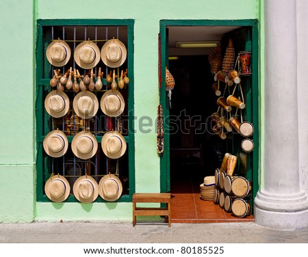 Facade of an old house selling hats, musical instruments,religious necklaces and other traditional craft in Havana - stock photo