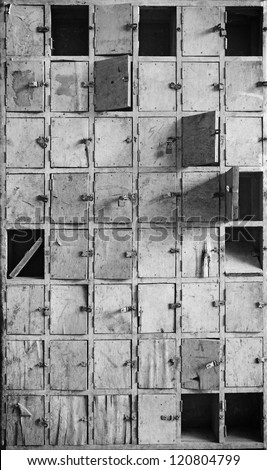 Facade of an old vintage timber postal box with locks and latch in monochrome, for textural background. - stock photo