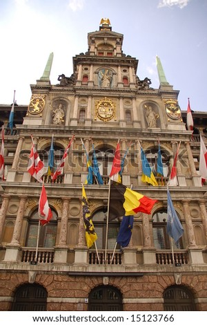 Facade of Antwerp city hall with flags - stock photo