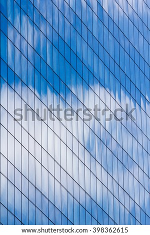 Facade of glass and steel with open window reflecting sky and clouds.