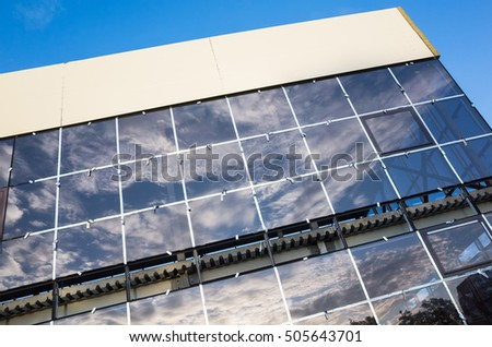 Facade of industrial building under construction, wall of blue shining glass. Common architecture example