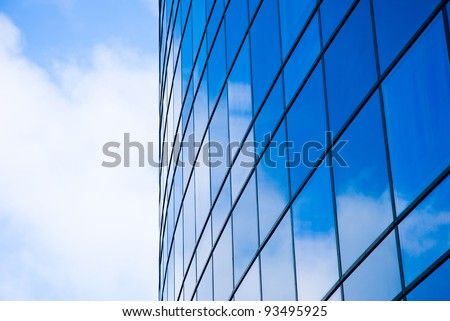 Facade of modern business building with reflection of cloudy sky in the windows. - stock photo