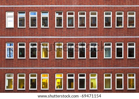 facade of office building in the evening with illuminated windows - stock photo