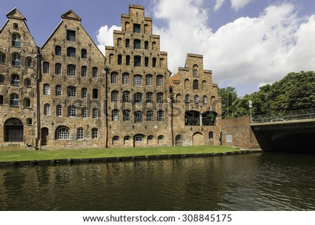Facade of old buildings near the river, in Lubeck, Germany - stock photo