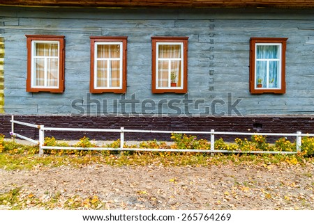 Facade of the old wooden house with windows in autumn. - stock photo