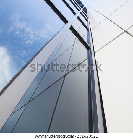 facade of white office building with reflections of very blue sky and clouds - stock photo