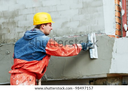 Facade Plasterer at outdoor wall renovation decoration with float - stock photo