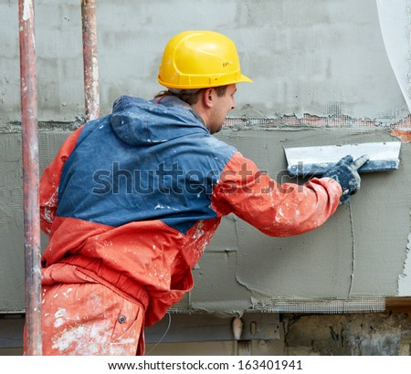 Facade Plasterer builder working at outdoor wall renovation decoration with float - stock photo