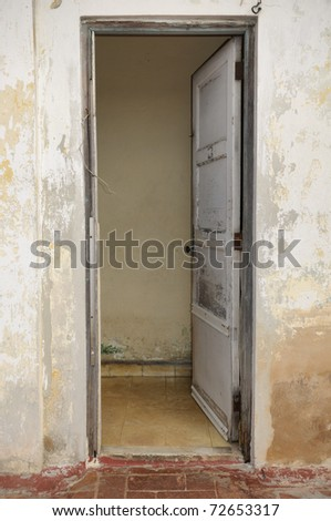 Facade with old wooden white door opened in shabby wall