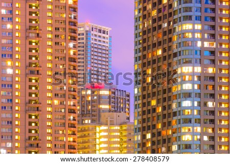 Facades and windows of high-rise buildings at night - stock photo