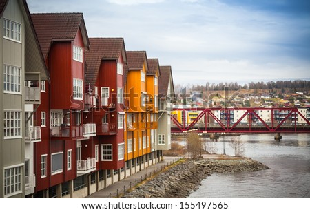 Facades of colorful wooden houses in small Norwegian town - stock photo