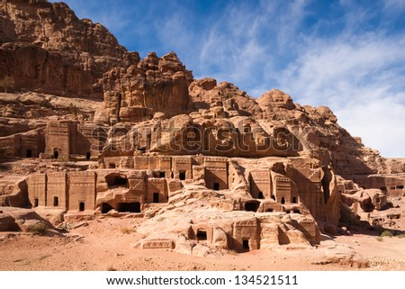 Facades of old rock houses against a blue sky with white clouds in ancient Petra in Jordan - stock photo