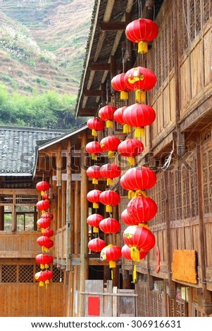 Facades of rustic wooden houses with red Chinese lanterns in Longji / Longsheng, China. Chinese people belief that the red lanterns bring happiness, love, peace and a long life - stock photo
