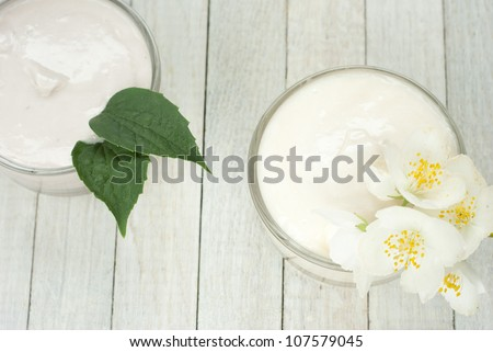 face and body cream moisturizers with jasmine flowers on white wooden, top view - stock photo