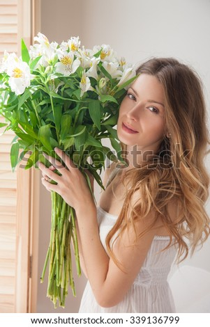 Face and flowers.Beautiful young woman in the early morning was awakened by the fragrance of flowers, the girl at the window in a big bouquet of flowers in her hands. girl in pajamas