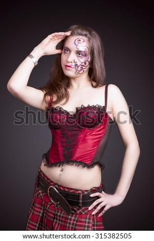 Face Art Concept: Portrait of Caucasian Female With Unique Face Art Painting. Posing In Corset Against Black.Vertical Image - stock photo