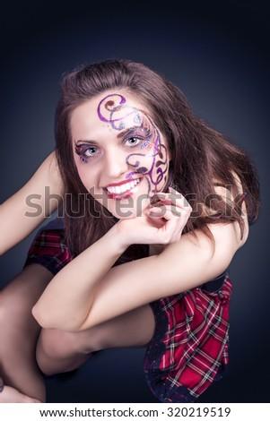 Face Art Concept: Portrait of Smiling Caucasian Female With Unique Face Art Painting. Posing In Corset Against Black. Horizontal Image Composition - stock photo
