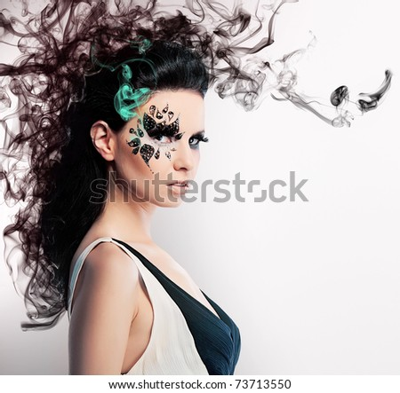 face art of rhinestones on brunette woman and smoke - stock photo