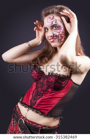 Face Art Project: Sexy Caucasian Brunette Woman In Corset Painted With Unique Face Art Painting.Against Black Background. Vertical Image Orientation - stock photo