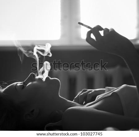 face beautiful girl smoking a cigarette - stock photo