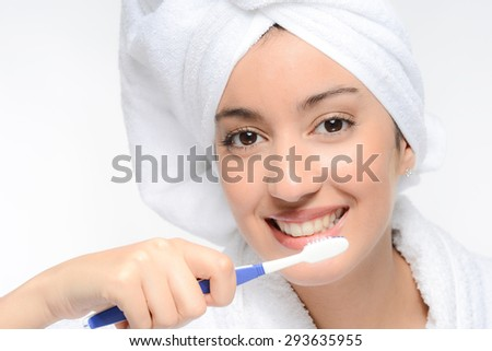 face close-up of a beautiful young brunette ethnic woman brushing her teeth - stock photo