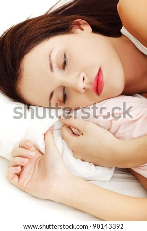 Face closeup of a beautiful young woman lying in bed, cuddling to the sheet and worrying.