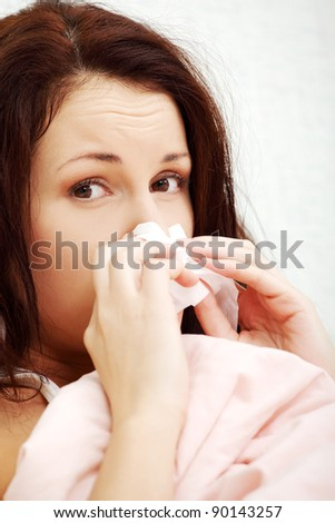 Face closeup of a beautiful young woman lying in bed, having a cold and sneezing in a tissue. - stock photo