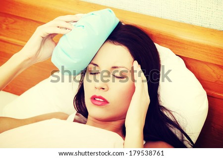 Face closeup of a young beautiful and fit woman suffering because of the headache, holding an ice-bag next to her forhead. - stock photo