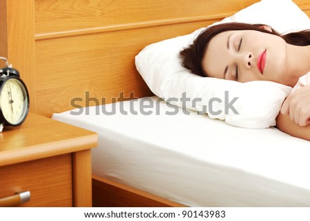 Face closeup of a young beautiful woman sleeping in bed, with a black alarm clock in the left site of the picture.