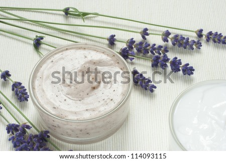 face cream and hand cream with blue lavender flowers on white textile background - stock photo