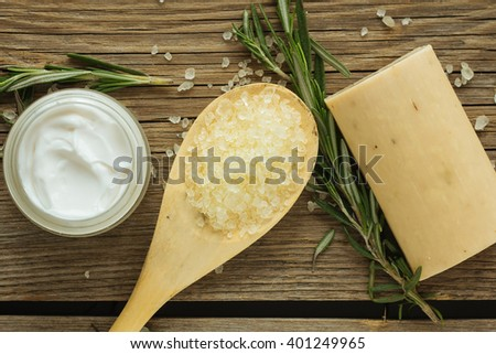 Face cream, sea salt, soap and rosemary top view selective focus - stock photo