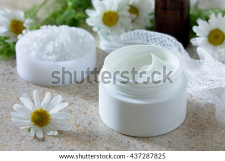 Face cream with chamomile essential oil bottle of aromatherapy and salt on brown stone background. Spa Chamomile. - stock photo