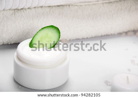 Face cream with cucumber and towel