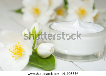 face cream with jasmine blossom on white wooden table