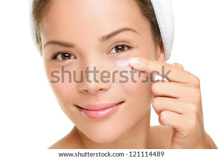 Face cream woman applying skin cream under eyes. Beauty eye contour wrinkle cream or anti-aging skin care cream. Beautiful young mixed race Asian  / Caucasian beauty model isolated on white background - stock photo