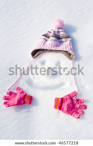 Face drawn in snow with cap, gloves and snowball. - stock photo