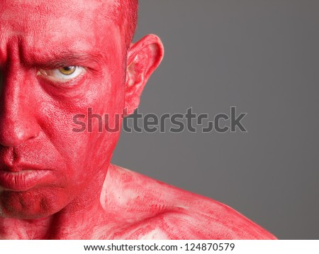 Face man makeup red on isolated background and looking at camera with seriously expression - stock photo