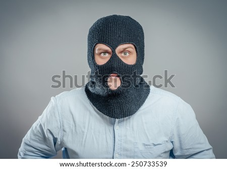 Face of a angry burglar wearing a black ski mask or balaclava  - stock photo