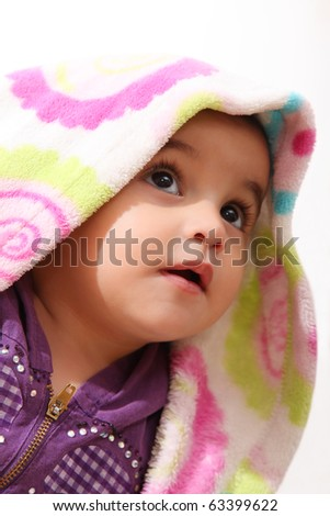 Face of a baby with a blanket over his head - stock photo