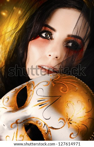 Face Of A Beautiful Female Performer With Dark Eyeliner Makeup And Perfect Eyelashes Holding Carnival Mask Against Glittering Gold Background - stock photo