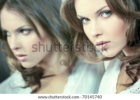 Face of a beautiful girl with her reflection in the mirror - stock photo