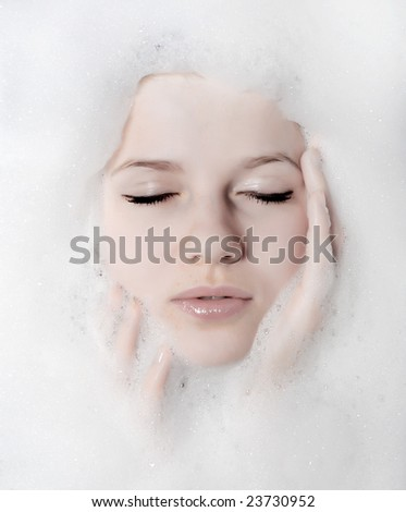 face of a beautiful woman in white foam - stock photo