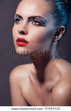 Face of a beautiful woman with creative makeup and red lips