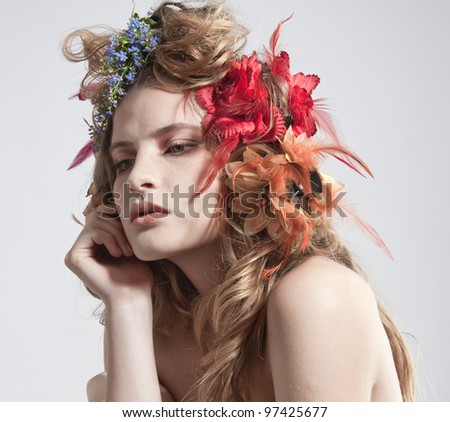 Face of a beautiful woman with summer flowers in her hair - stock photo