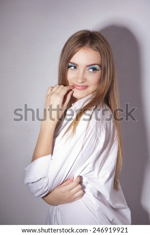 Face of a beautiful young woman with brightly blue eyes in white shirt - stock photo