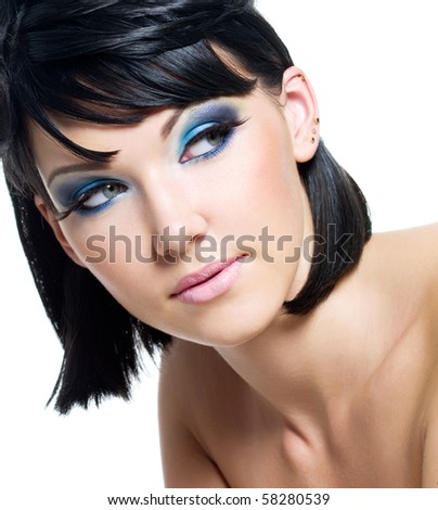 Face of a beautiful young woman with brightly blue make-up. Isolated on white - stock photo