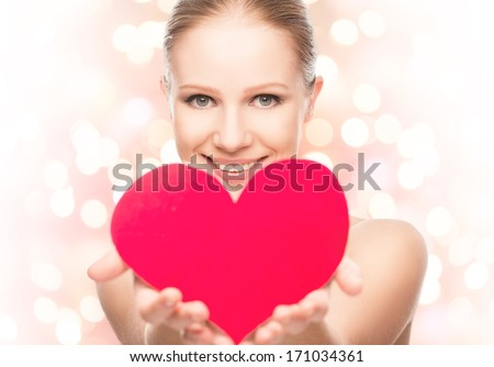 face of a beautiful young woman with red heart symbol of love - stock photo