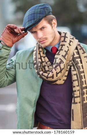 face of a fashionable young man holding his hat and looking at the camera - stock photo