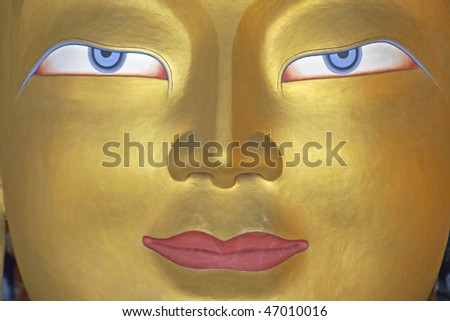 Face of a golden Buddha inside a temple at Thikse monastery. Ladakh, India