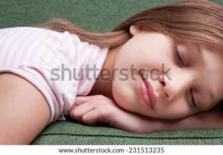 face of a little sweet girl sleeping on a green sofa and dreaming
